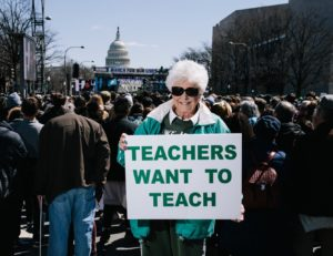 "A woman stands with a sign that says ""Teachers Want to Teach"" at the March For Our Lives."