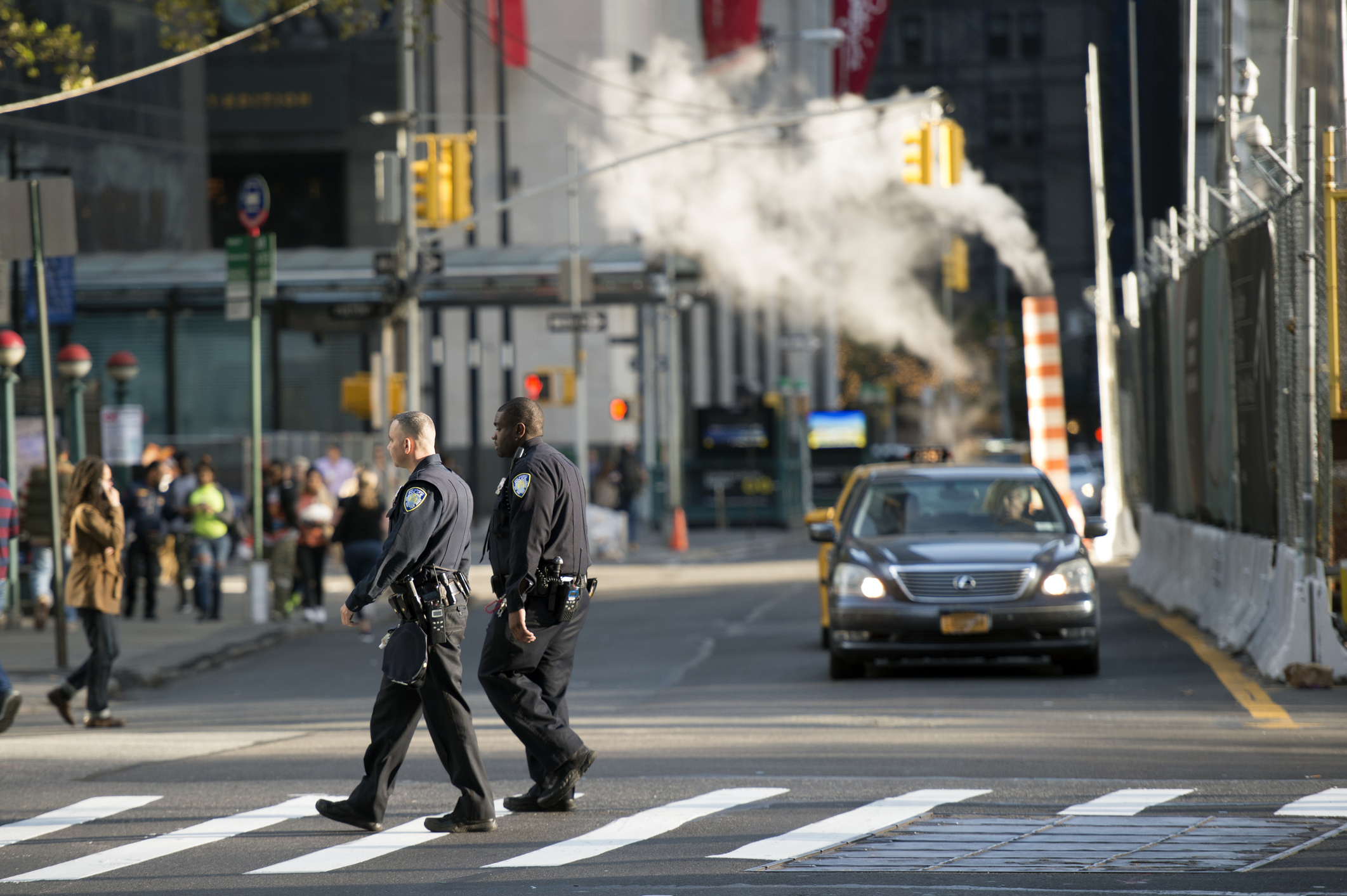 Two police officers are crossing the street near the World Trade Center 'Ground Zero' in Manhattan, New York. Blurred skyscrapers and steam coming out of the manholes in the background.